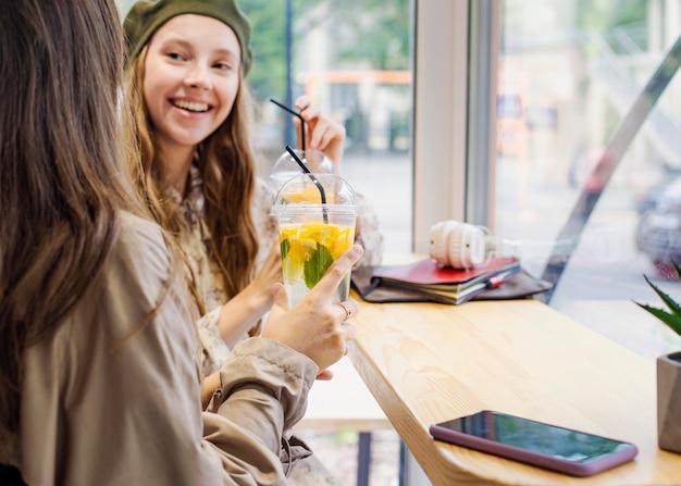 カフェで新鮮な飲み物を持っている友達