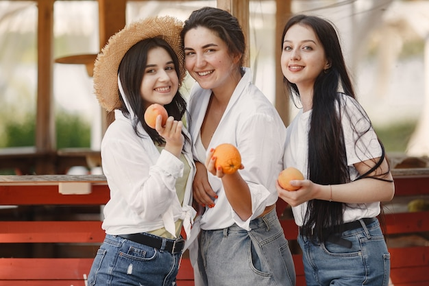 Friends with fruits. girl in a hat. woman in a white t-shirt.