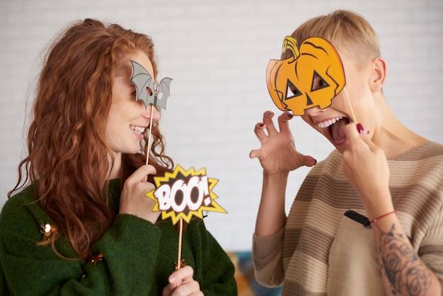 面白いハロウィーンのマスクを持つ友達
