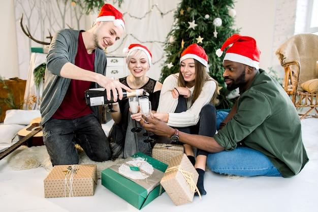 Друзья в новогодних шапках празднуют рождество с шампанским