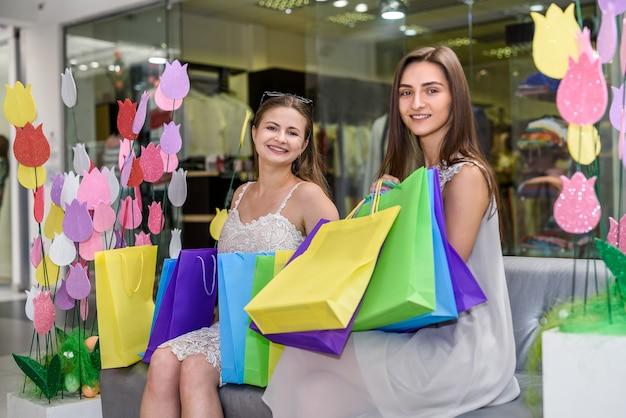 ショッピングモールのソファで休んでいる買い物袋と友達