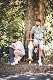 Friends with skateboards in forest