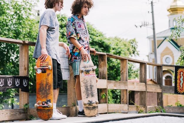 Друзья с скейтбордами на рампе