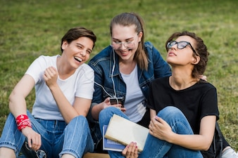 Friends with smartphone resting on park lawn