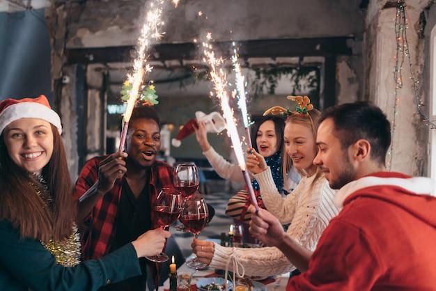 線香花火を手にした友達。一緒にクリスマスイブを祝う友人のグループ。