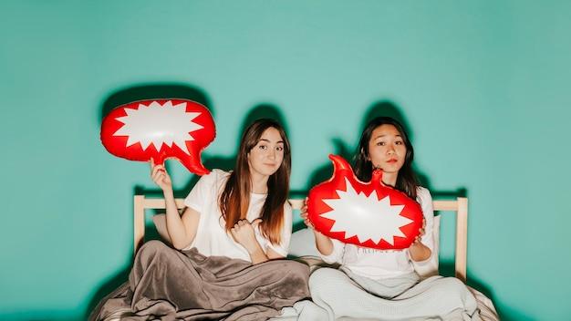 Amici con palloncini di discorso a letto
