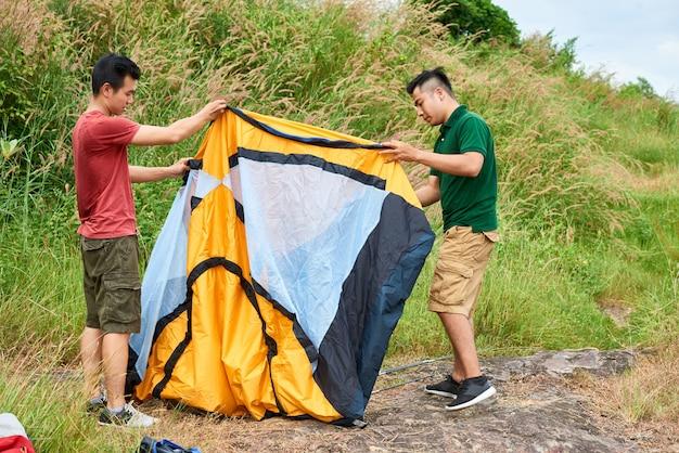 Amici con una tenda da campeggio