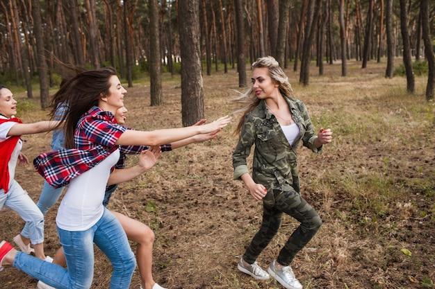 競争の概念を実行している友人の女性グループ。自然の中でスポーツゲームを追いかけます。