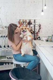 Друзья. молодая женщина-владелец домашнего животного держит свою собаку и чувствует себя счастливой