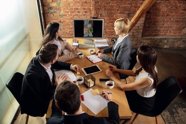 Друзья. молодые люди разговаривают, работают в режиме видеоконференции с коллегами, коллегами в офисе или гостиной. интернет-бизнес, обучение при утеплении, карантин. работа, финансы, техническая концепция.
