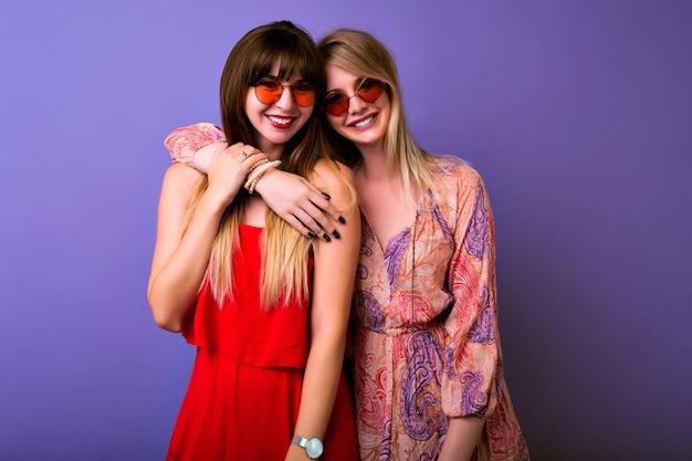 우정과 의사 소통 개념, 두 자매 최고의 잎 여자는 유행 여름 옷장과 일치하는 colocar를 착용하고 카메라, boho 안경, 보라색 배경에 포옹하고 보인다.