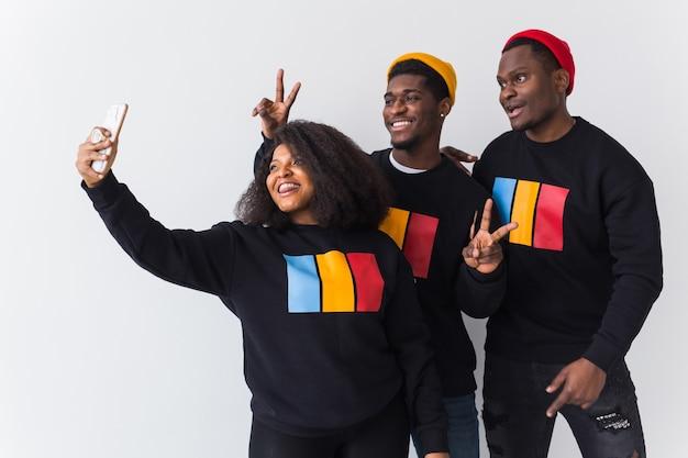 Концепция дружбы и веселья. группа друзей афро-американских мужчин и женщин, делающих селфи на белом