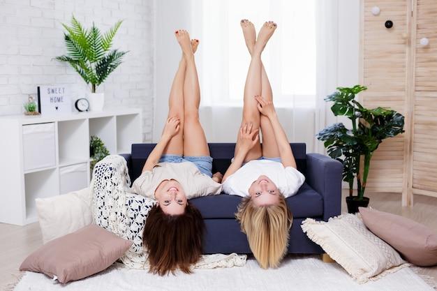 Концепция дружбы и домашней вечеринки - две молодые красивые женщины, лежа на диване с поднятыми ногами