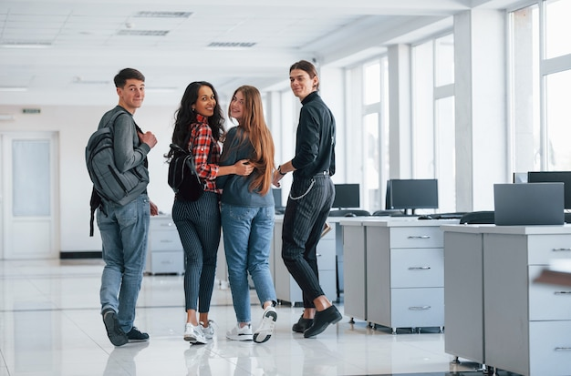 우정과 포옹. 휴식 시간에 사무실에서 걷는 젊은 사람들의 그룹입니다.
