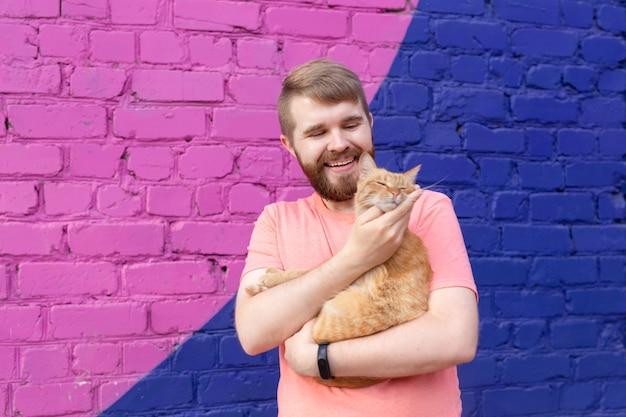 우정과 애완 동물 개념 - 야외에서 귀여운 고양이와 함께 잘생긴 젊은 남자