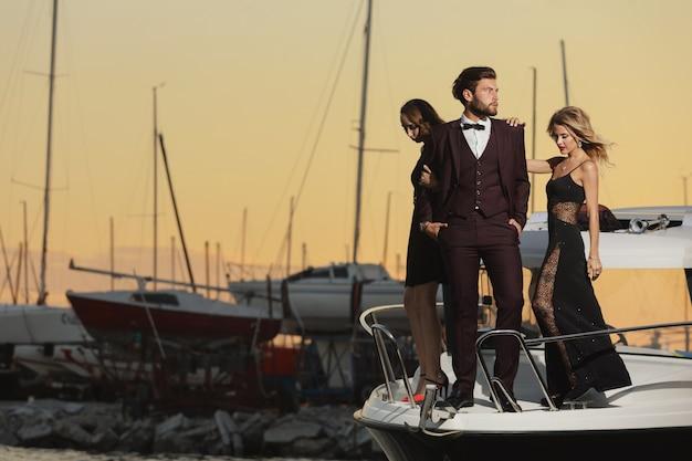友情と休暇。ヨットでのパーティー。海を航海する甲板上の若者のグループ。