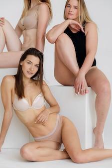 분홍색 배경의 고품질 사진 위에 흰색 속옷이 다른 행복한 여성의 우정의 아름다움 신체 긍정적인 사람들 개념 그룹