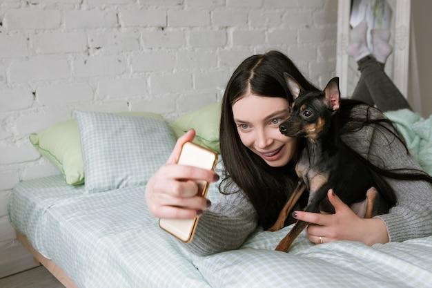 犬と飼い主の友情。小さな子犬と孤独な女性、女の子はペットと一緒に自分撮りをします