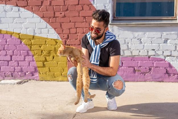 화려한 벽 야외 배경에서 남자와 고양이 사이의 우정.