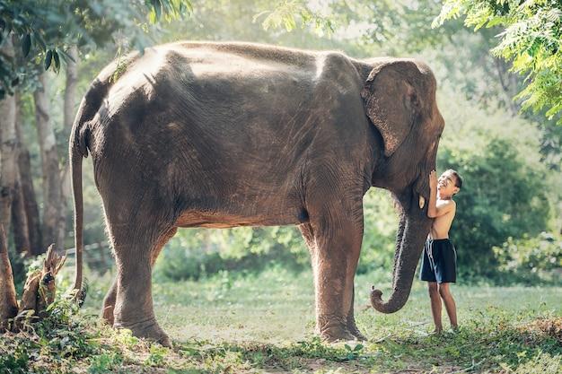 Friendship between children with elephant at countryside of thailand