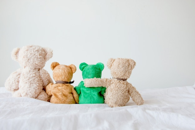 Friendship -four teddy bears holding in one's arms