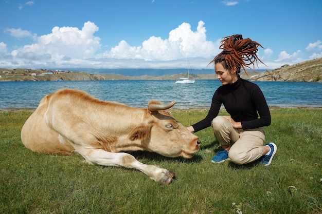 Friendship between girl with dreadlocks and beige cow on a field near water