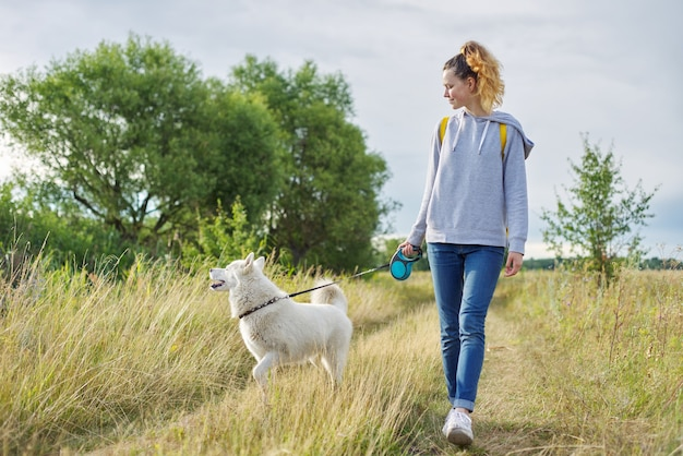 Friendship girls and dogs, teenager and pet husky walking outdoor, beautiful landscape nature meadow cloudy sky