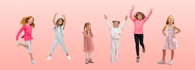友情。ピンクのスタジオの背景にカラフルなカジュアルな服を着てジャンプする小学生や生徒のグループ。クリエイティブなコラージュ。学校に戻る、教育、子供の頃の概念。陽気な女の子。