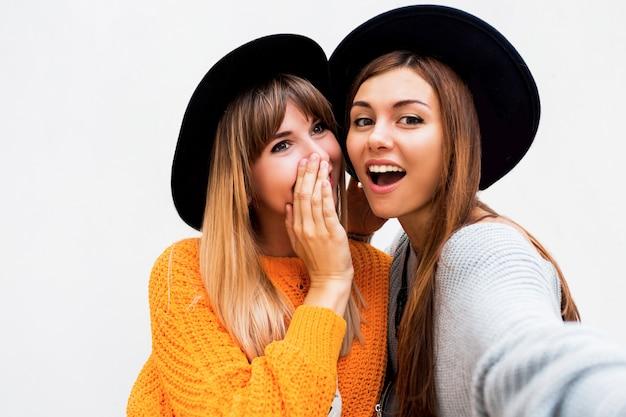 友情、幸福、人々の概念。白のゴシップをささやく二人の笑顔の女の子