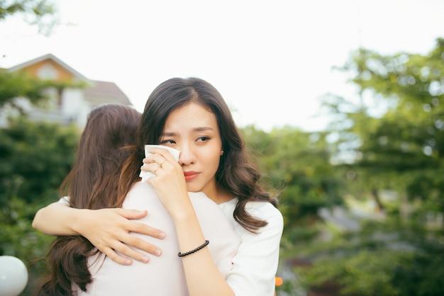 Дружба поможет поддержать. подавленная азиатская женщина, обнимая своего друга.