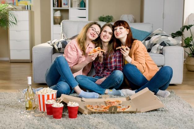 友情、休日、ファーストフード、お祝いのコンセプト-ドリンクとポップコーンを家でピザを食べて、居心地の良い部屋の床に座って幸せな若い女性の友人