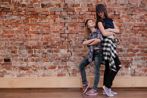 스타일의 우정. 도시 춤. 십대를위한 힙합, 스튜디오에서 세련된 행복한 소녀. 여유 공간이있는 벽돌 벽 배경. 즐거운 거리 생활, 패션 컨셉