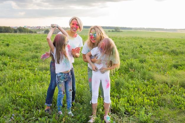 Концепция дружбы, индийских праздников и людей - молодые женщины и дети веселятся летом