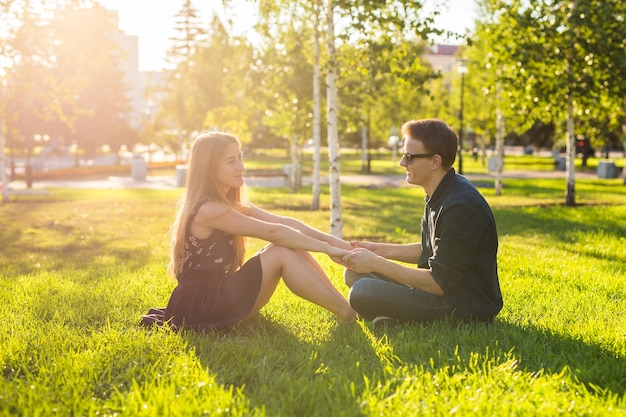 Friendship, leisure, summer and people concept. young couple relaxing on a meadow.
