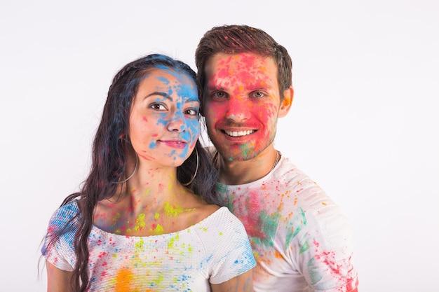 Дружба, любовь, фестиваль холи, концепция людей - молодая пара играет с цветами