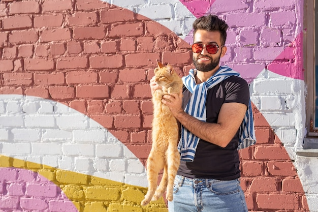 Friendship between man and cat on background of colourful wall outdoor