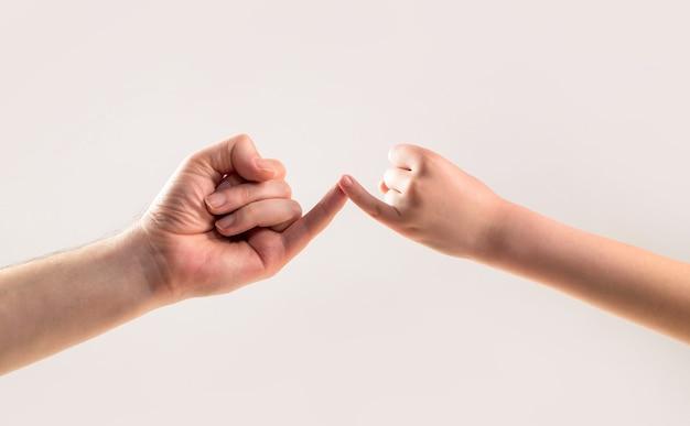 世代の友情。父、娘の手作りの約束の友情の概念。子供は小指を一緒に引っ掛けます。両手の小指が一緒に保持します。友情と許しを示してください。
