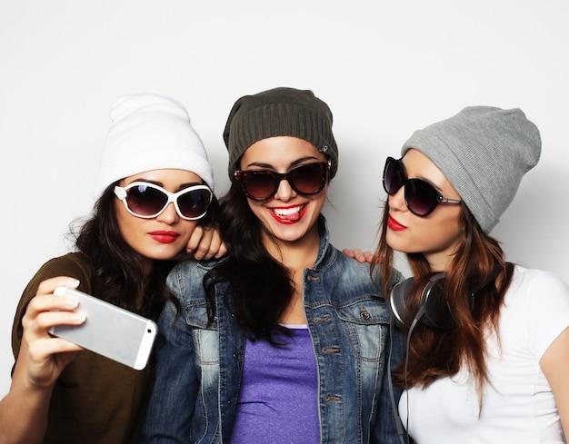 Концепция дружбы, людей и технологий - три счастливые девочки-подростки со смартфоном, делающим селфи