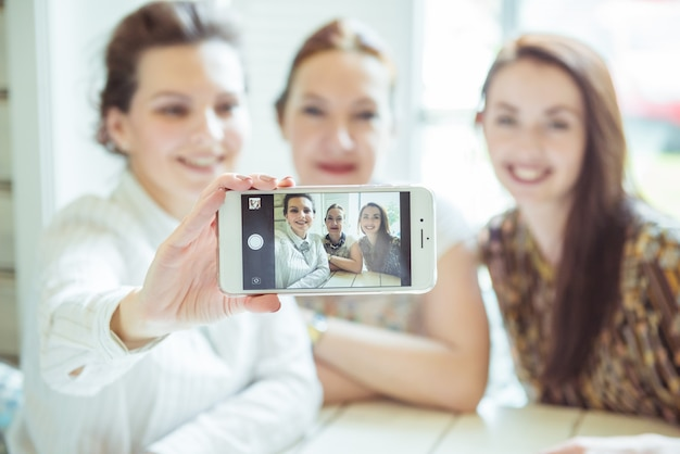 Friendship, people and technology concept - happy friends or teenage girls with smartphone taking selfie
