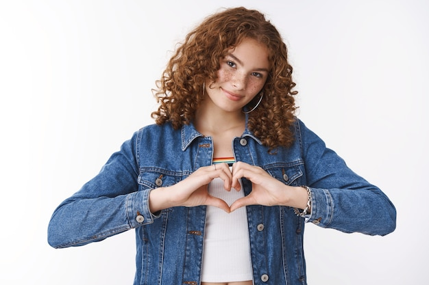 Friendship, relationship lifestyle concept. charming friendly european redhead curly-haired girl show love sign make heart near chest tilting head smiling expressing sympathy, white background
