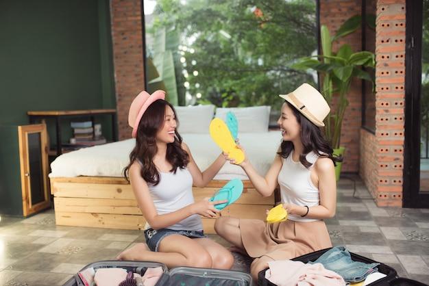 우정. 여행. 휴가를 가기 전에 여행 가방을 포장하는 두 아시아 젊은 여자 친구