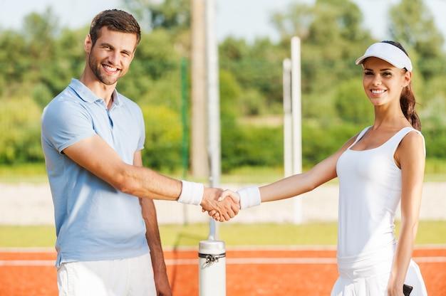 우정이 이깁니다. 두 명의 자신감 있는 테니스 선수가 테니스 네트 근처에 서서 악수하고 웃고 있습니다.