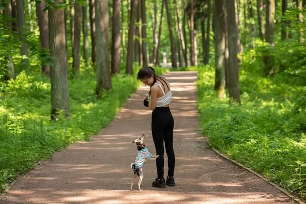 애완 동물과의 우정. 주인이있는 귀여운 강아지가 공원에 서 있습니다.