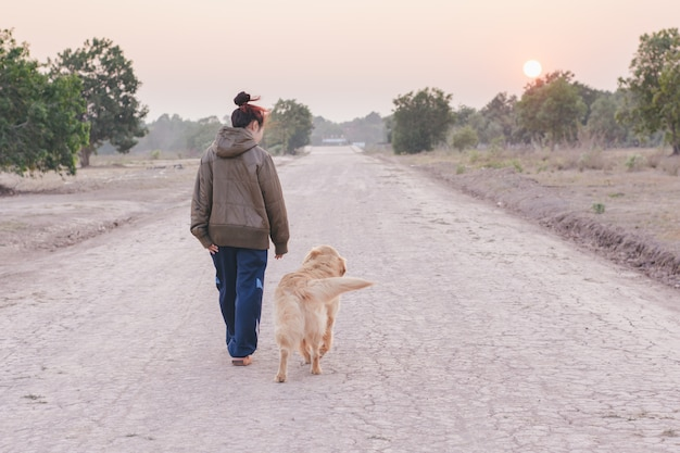 Friendship woman and dog golden walking