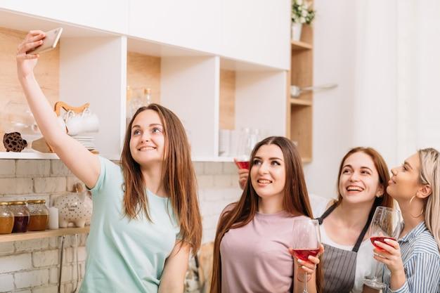 楽しみを集めるフリーンズ。夜のレジャーリラクゼーション。自撮りをしている興奮した若い女性。グラスに赤ワイン。