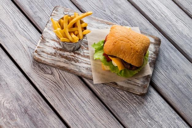 선상에서 감자 튀김과 버거. 빵과 양상추 잎. 패스트 푸드 요리의 예. 치즈버거의 비밀 레시피.