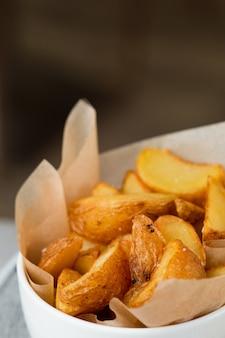 Жарит крупный план картофеля с крафтовой бумагой. айдахо картофель крупным планом.