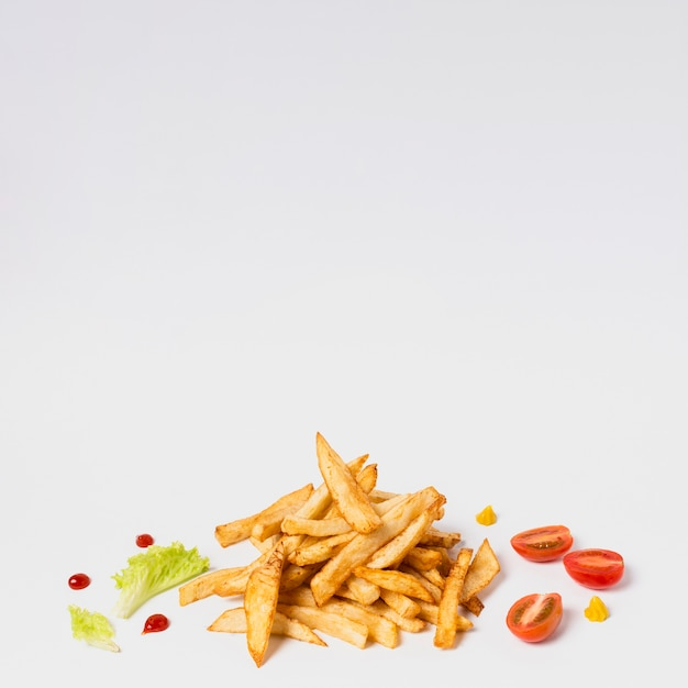 Fries with tomatoes on white table