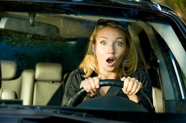 자동차를 운전하는 여자의 얼굴을 두려워하고 바퀴를 강하게 쥐어 짜십시오.
