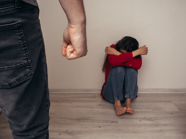 Frighted girl in a red shirt against the wall and man with fists clutched